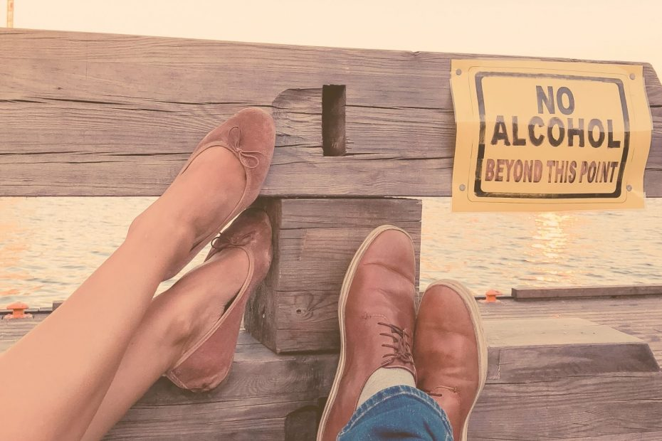 "woman and man feet on bench near sign reading ""no alcohol beyond this point"""