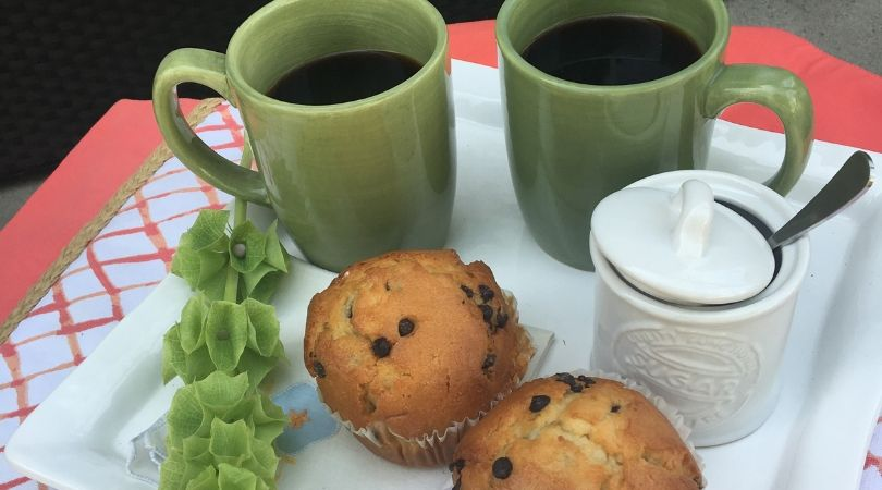 white platter with green coffee mugs and muffins