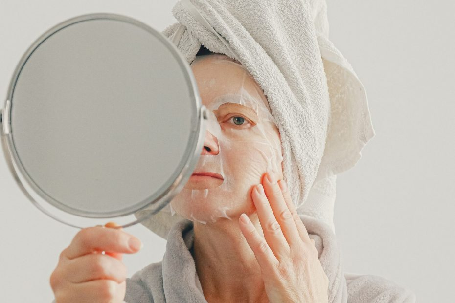 woman looking in hand-held mirror and wearing facial mask and towel over her hair