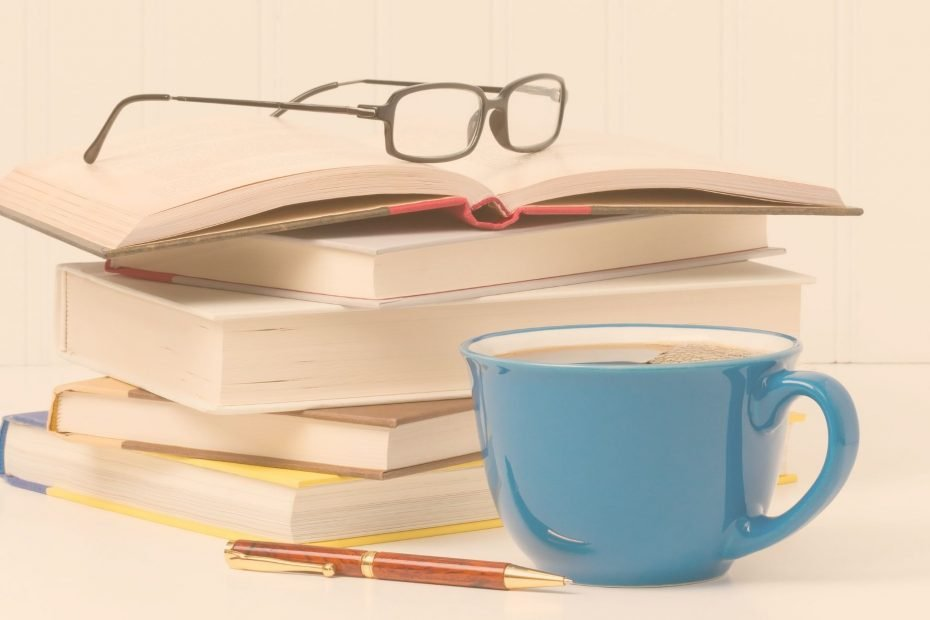 stack of books, pen, glasses, and cup of coffee in blue mug