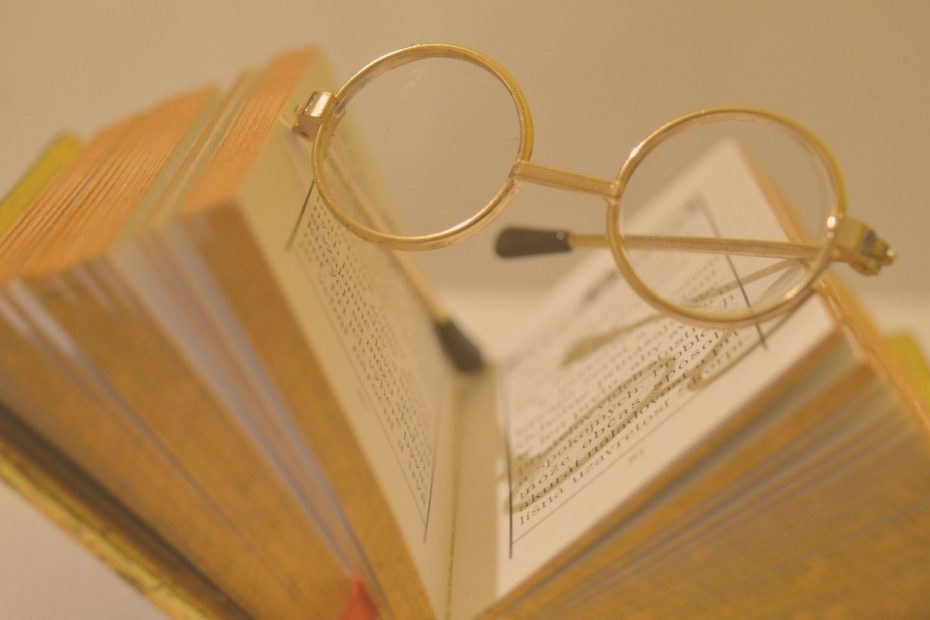 old book and round rimmed glasses