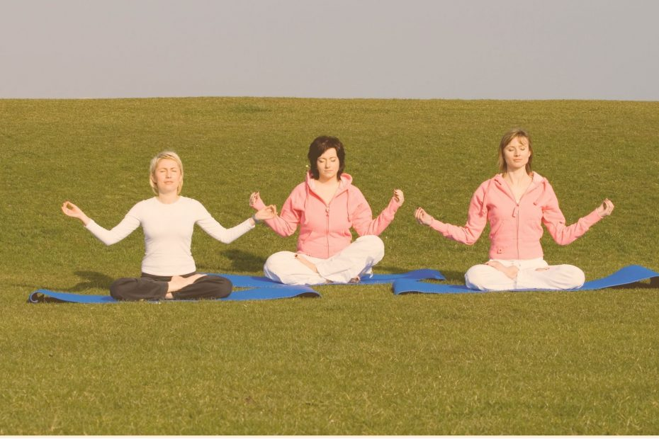 3 women meditating in a field
