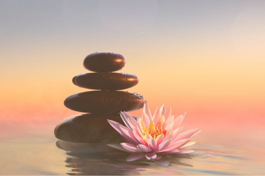 rock stack and lotus blossom in front of sunset