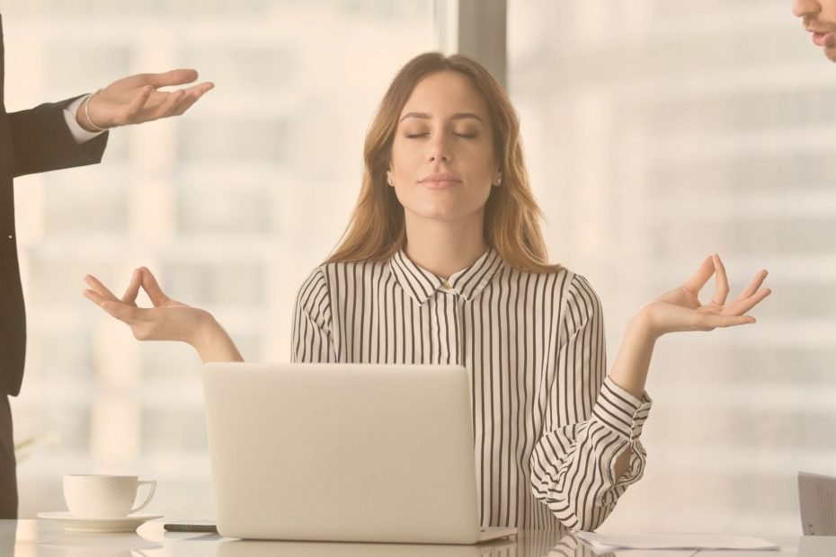 woman meditating at work while two men harrass her