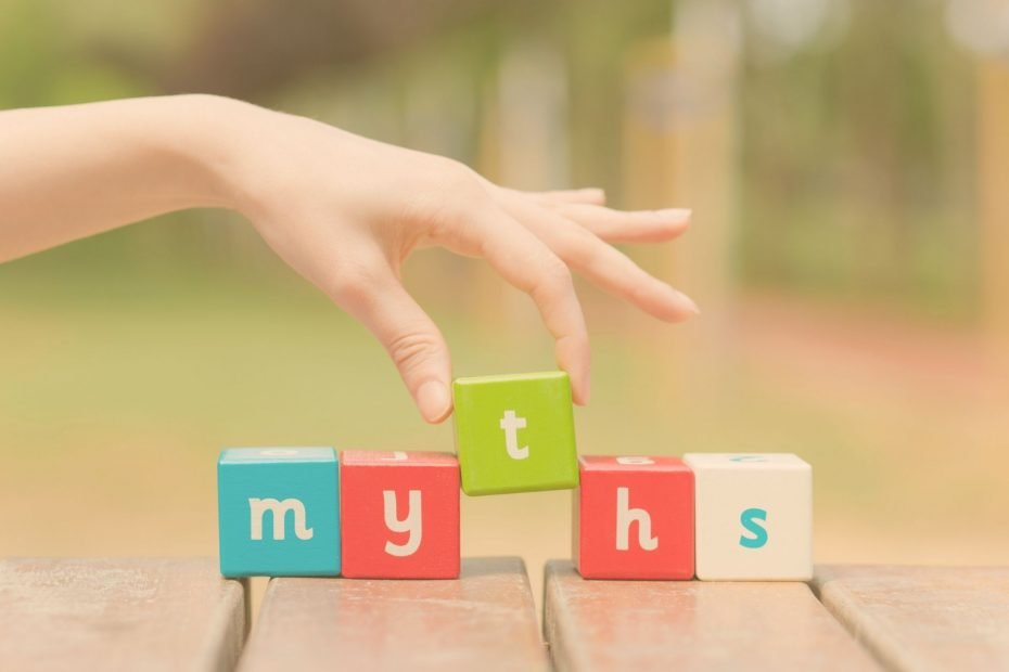 hand spelling out the word myth in colored blocks