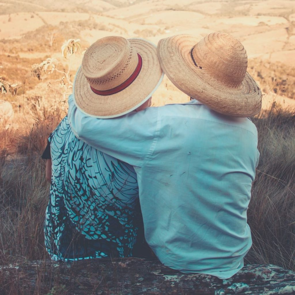 Older couple facing away from camera, sitting and hugging while wearing blue shirts and big hats