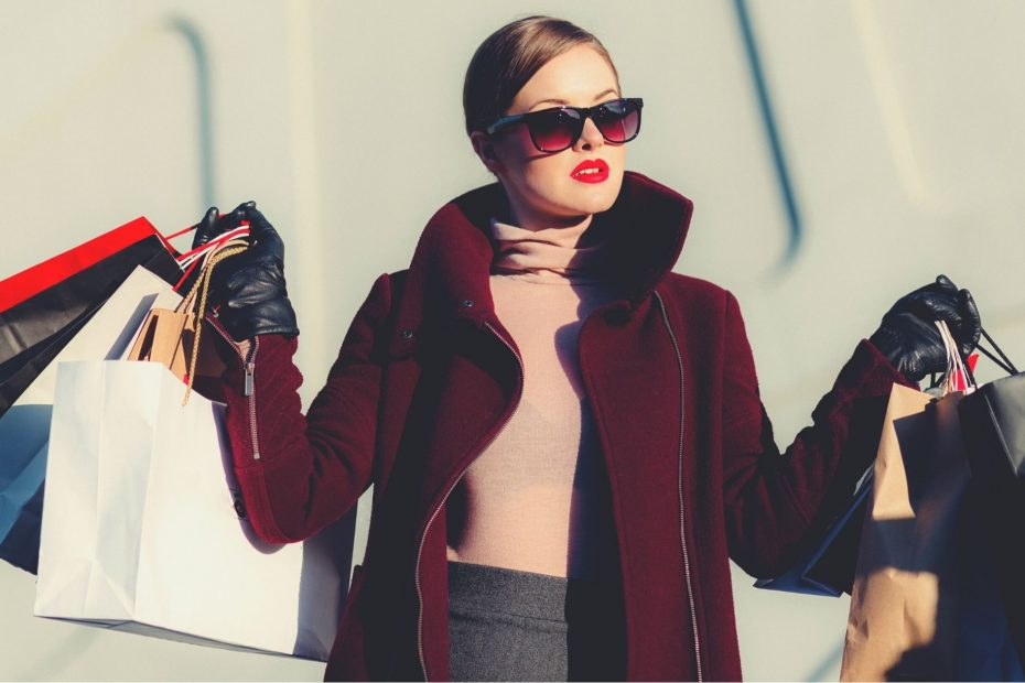 glamorous woman in red coat holding shopping bags