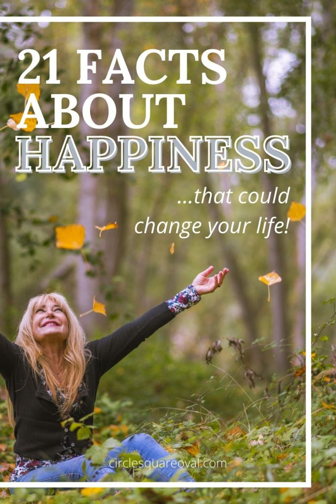 woman smiling while tossing fall leaves and thinking about facts about happiness