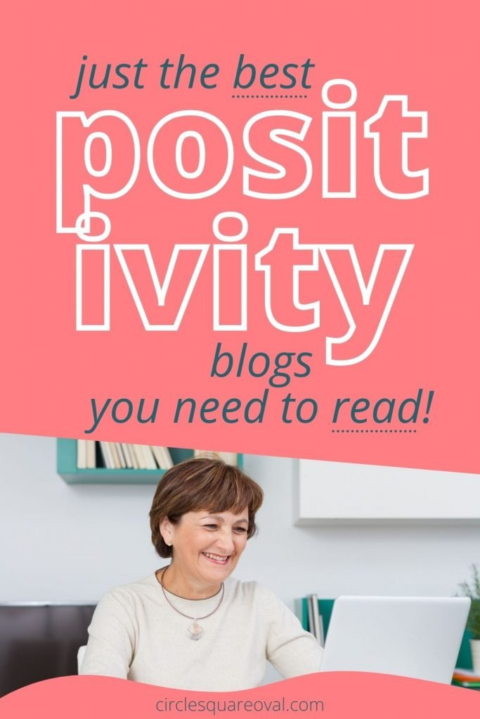 Woman smiling while reading computer, best positivity blogs