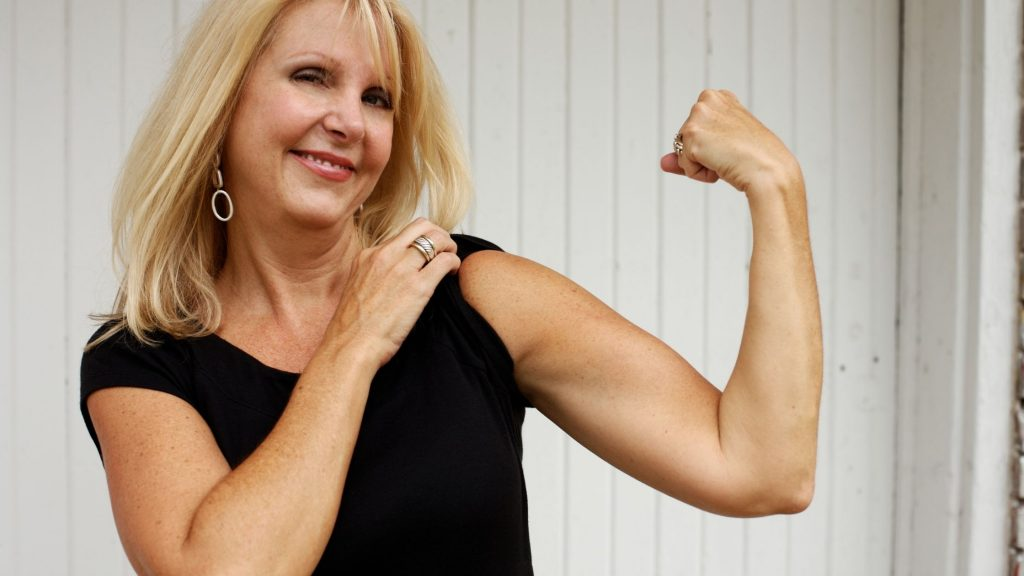 blonde woman in black shirt flexing arm muscle