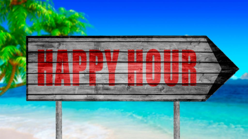 """sing reading """"happy hour"""" on beach in front of ocean"""