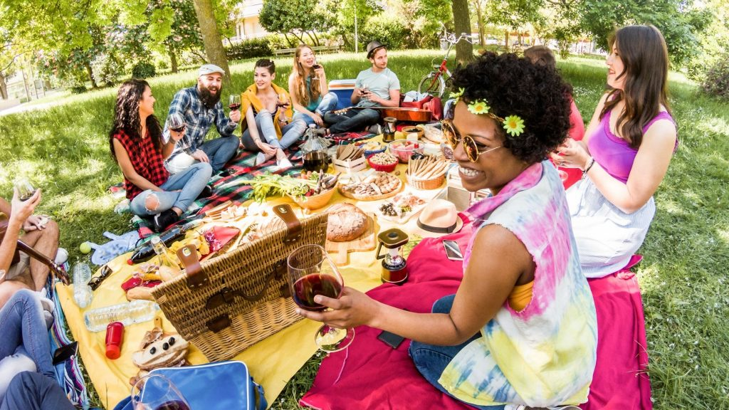 group of friends having a picnic under trees, acts of kindness to neighbors