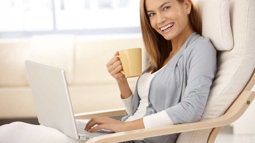 happy woman smiling, drinking from yellow cup and working on computer