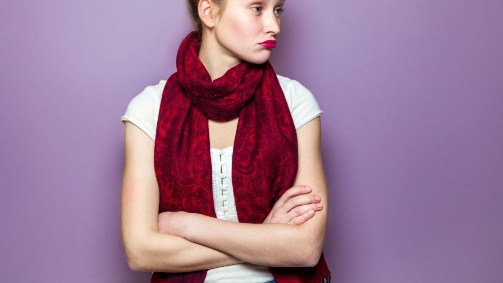 woman in burgundy scarf with crossed arms looking sad and alone