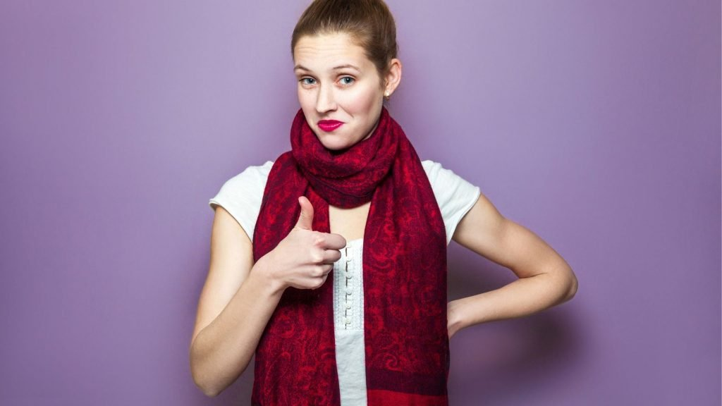 woman in burgundy scarf giving a thumbs up