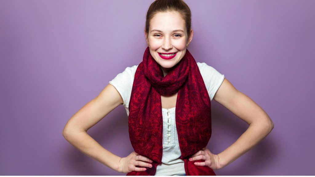 woman in burgundy scarf with big smile, looking happy