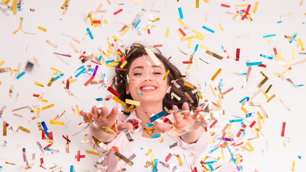 happy woman with multi colored confetti