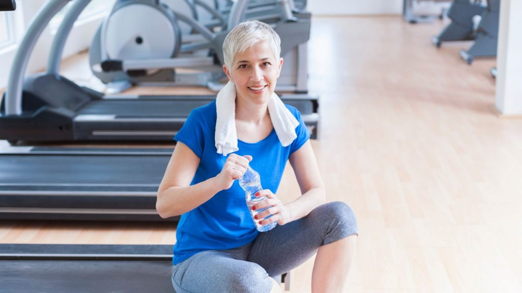 woman getting drink of water, towel around her neck, sitting on treadmill.  motivation for workout and eating healthily