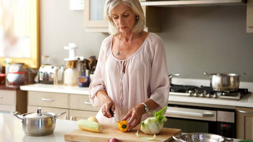 healthy woman in kitchen chopping vegetables