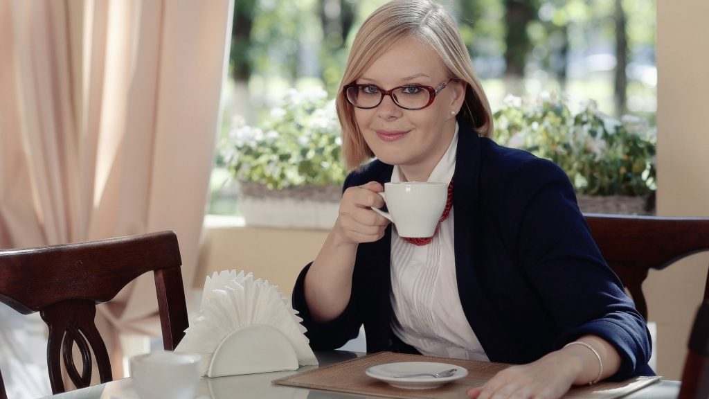 woman in black jacket with glasses sitting at table drinking a cup of tea