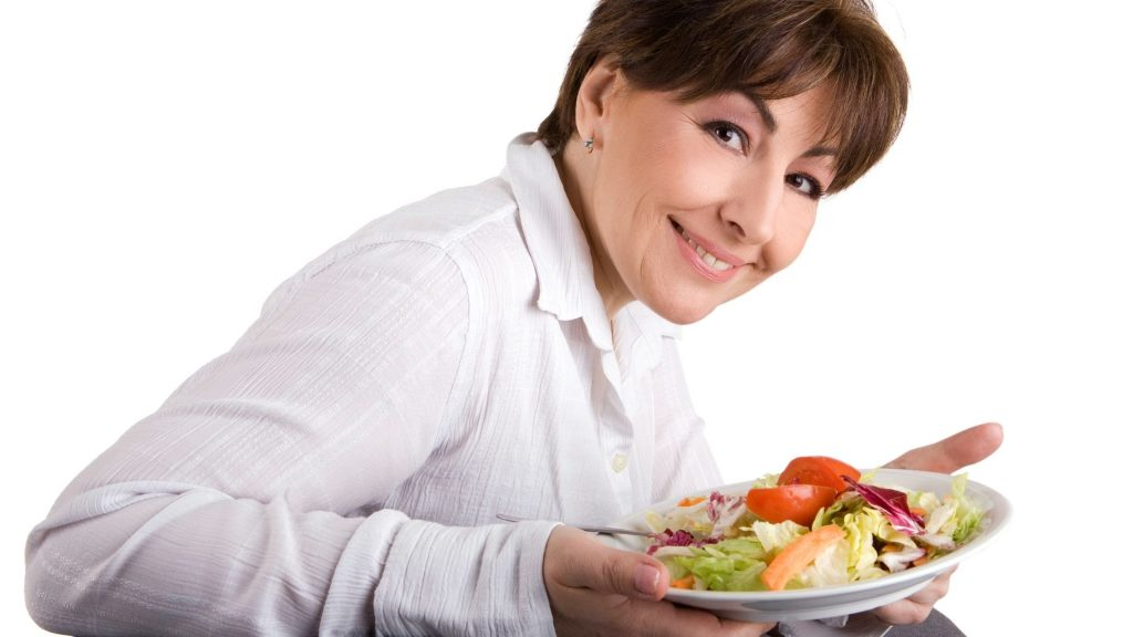 woman in white shirt smiling at camera, managing stress by eating a healthy salad