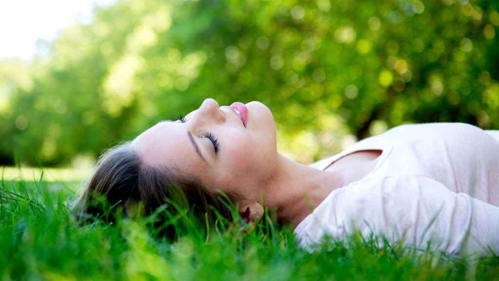 woman lying on back in grass with sun shining down, managing stress with healthy lifestyle