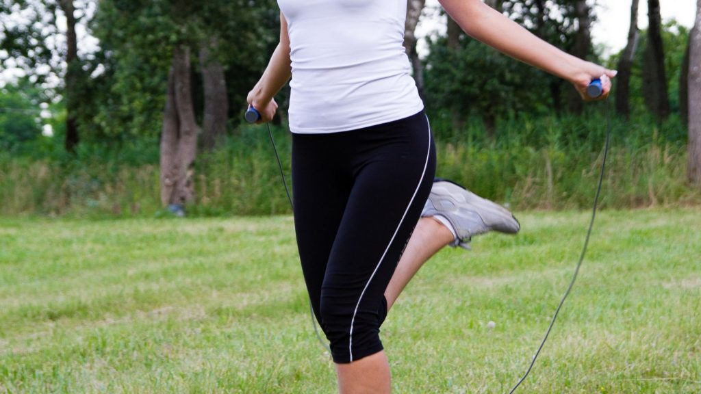 woman dressed in black and white workout clothes jumping rope in a field