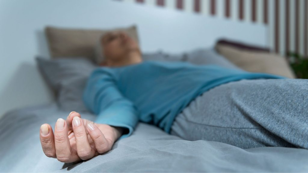 woman in blue sweats lying on bed on back, meditating