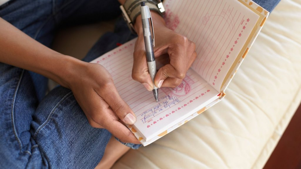 woman's hands holding pen and writing in journal as she sits on a white pillow