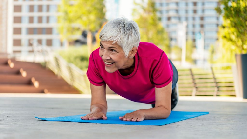 woman doing plank and smiling, motivation for workout and eating healthily