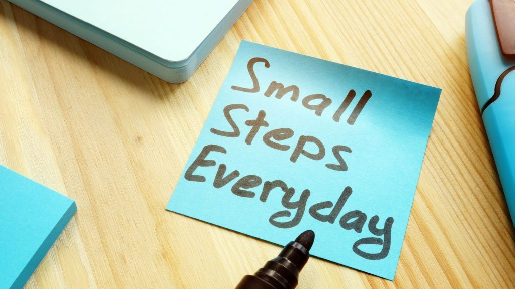 """blue postit note on desk that reads """"small steps everyday"""""""