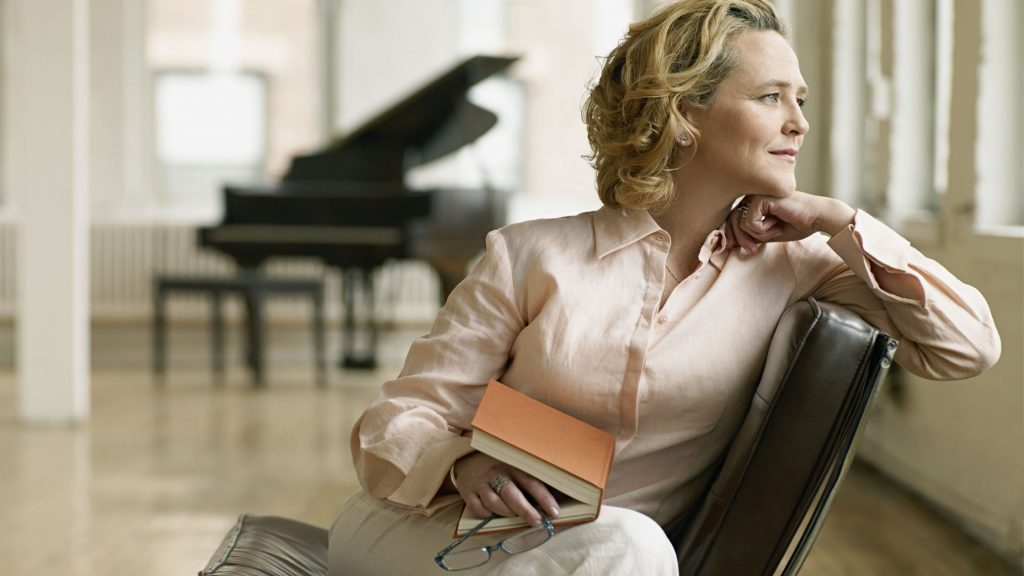 woman in chair with book, but gazing out window lost in thought