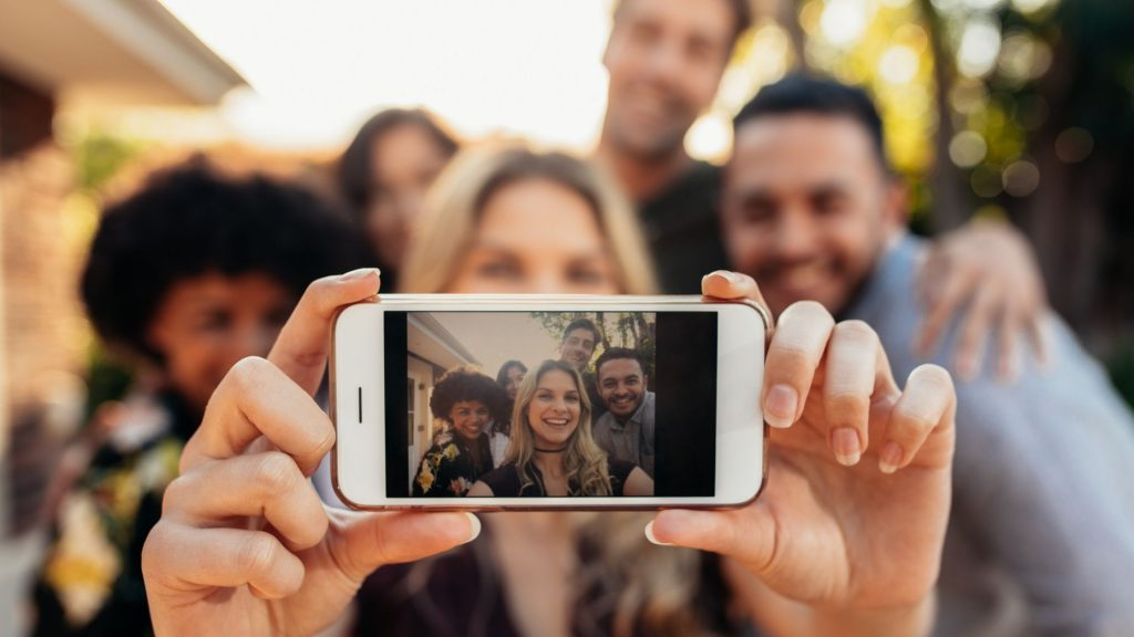 group of neighbors at pop up party taking group selfie