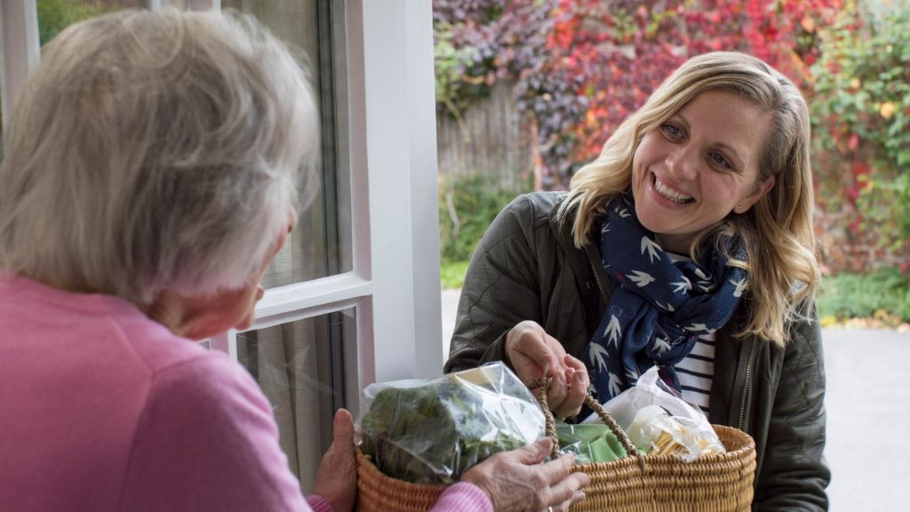 woman dropping off basket of food to elderly neighbor, what is kindness