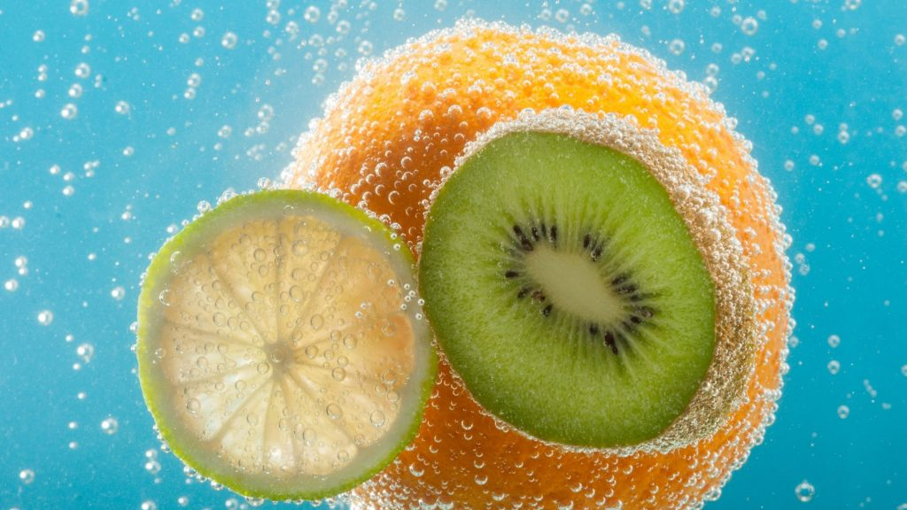 orange and kiwi floating in bubbly blue water