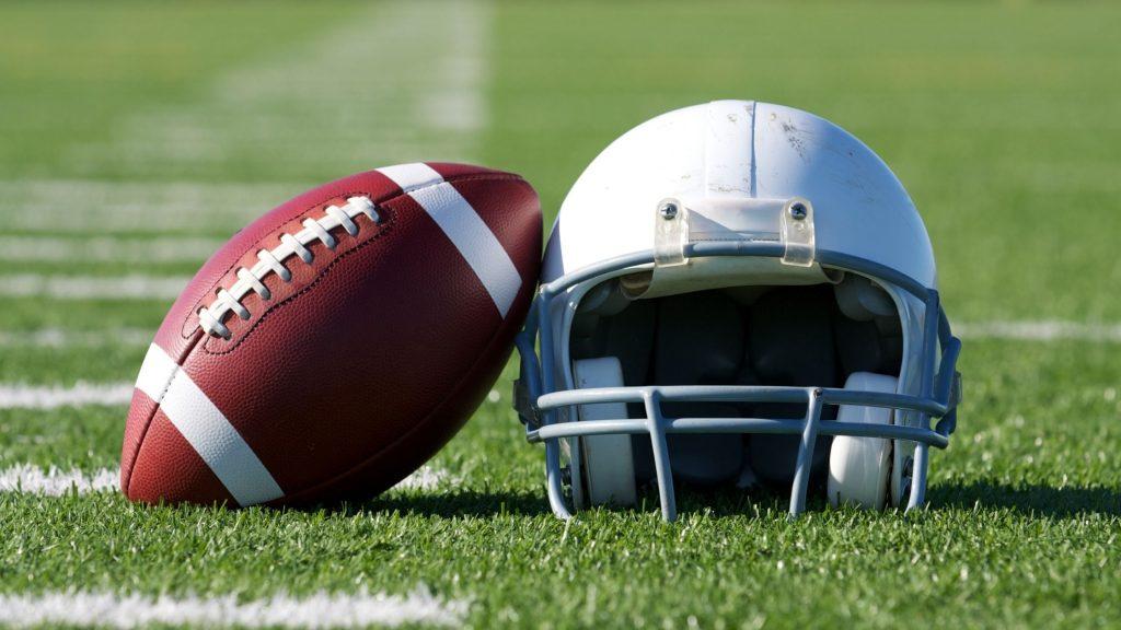 football helmet and football on 50 yard line