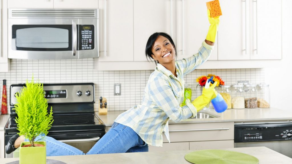 happy woman kicking feet up because kitchen is clean