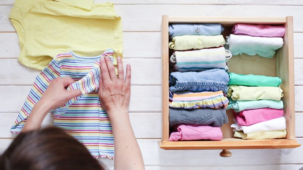 woman folding baby clothes