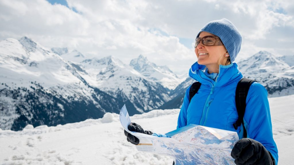 woman surrounded by snowy mountains, wearing blue ski gear and consulting map