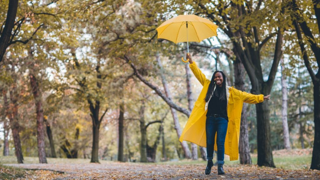 woman with yellow raincoat and yellow umbrella and big smile dancing in the rain