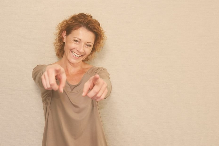 confident woman smiling and pointing at camera