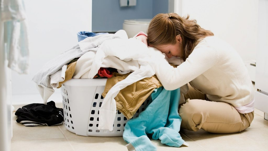 overwhelmed woman sitting on floor with face in huge pile of laundry