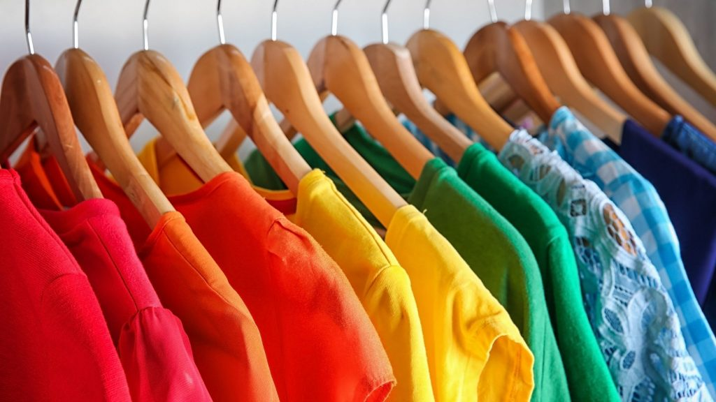 color coded tops in closet on wooden hangers