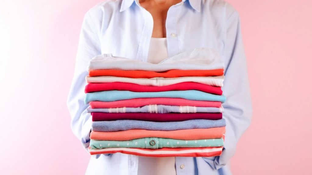 woman with neatly folded pile of laundry and rosy aura behind her