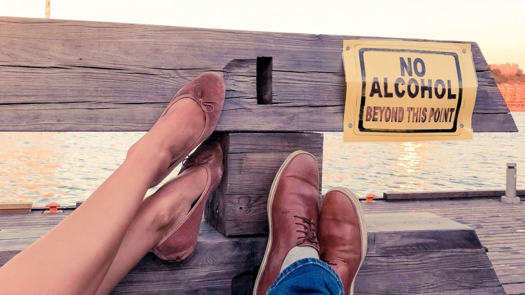 """feet of man and woman propped up on bench near sign reading """"no alcohol beyond this point"""""""