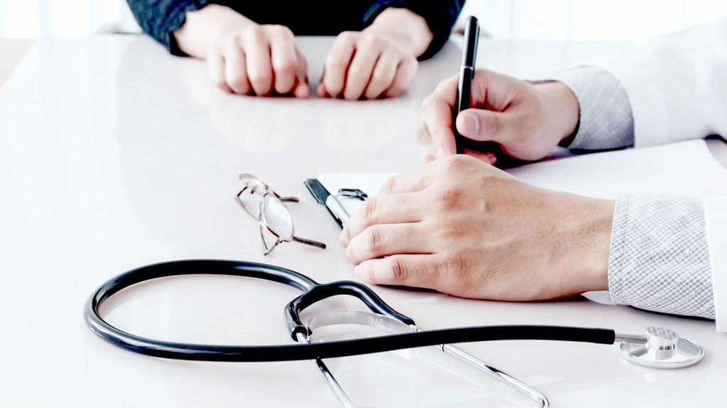 hands of doctor and patient and stethoscope