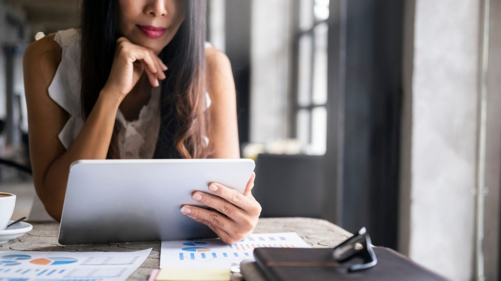 woman on computer learning about investments, importance of self-care as young adult
