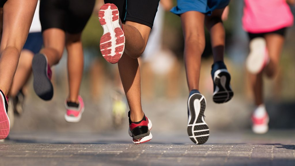 legs of runners at full stride, exercising for charity