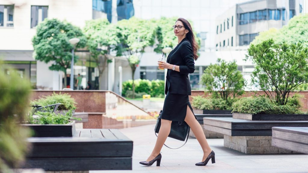 woman in black suit walking confidently outdoors in city, how to act confident even when you're not