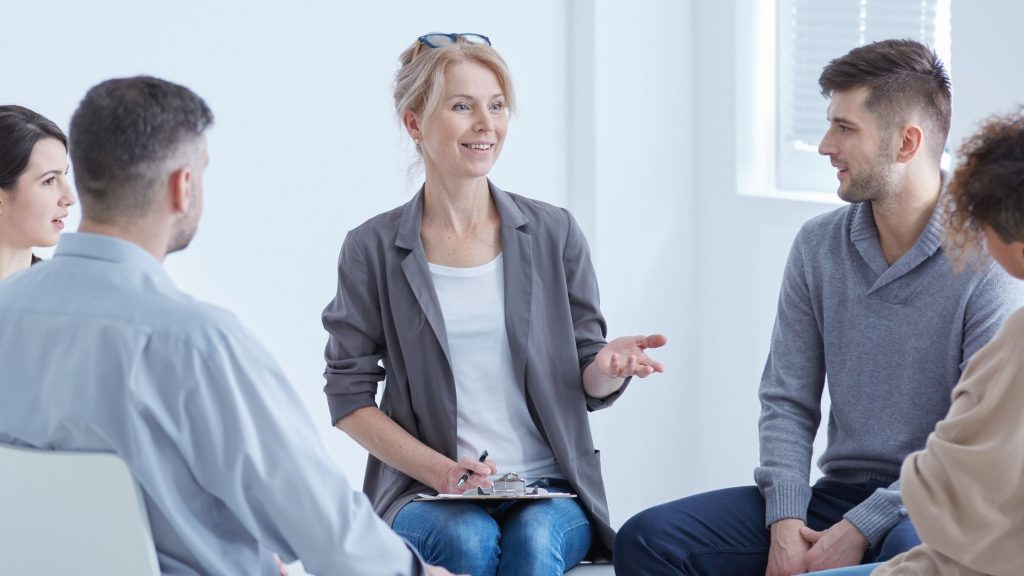 woman smiling and speaking confidently to a small group of others